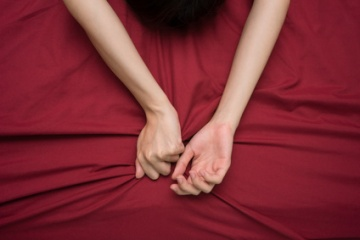 hand grasping on bed sheet